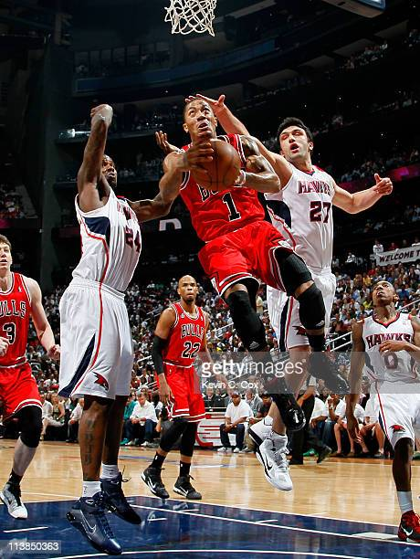 Derrick Rose of the Chicago Bulls drives under the basket against Marvin Williams and Zaza Pachulia of the Atlanta Hawks in Game Four of the Eastern...