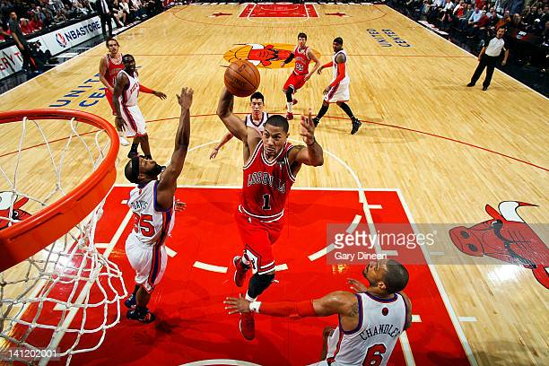 Derrick Rose of the Chicago Bulls dunks against Baron Davis and Tyson Chandler of the New York Knicks on March 12 2012 at the United Center in...