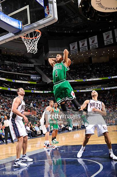 Derrick Rose of the Chicago Bulls dunks against Kris Humphries and Deron WIlliams of the New Jersey Nets during the game on March 17 2011 at the...