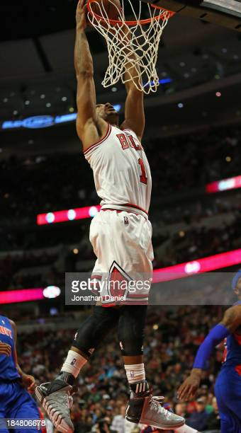 Derrick Rose of the Chicago Bulls dunks against the Detroit Pistons during a preseason game at the United Center on October 16 2013 in Chicago...