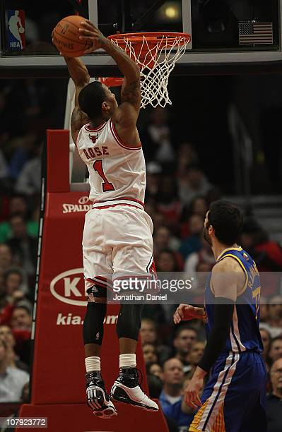 Derrick Rose of the Chicago Bulls goes up for a dunk over Valdimir Radmanovic of the Golden State Warriors at the United Center on November 11 2010...