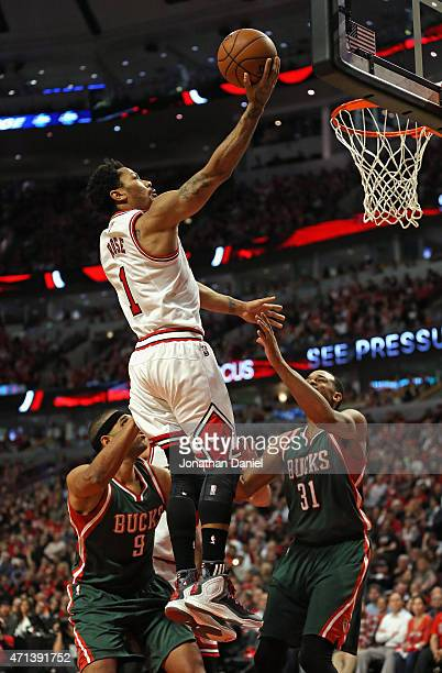 Derrick Rose of the Chicago Bulls goes up for a shot over Jared Dudley and John Henson of the Milwaukee Bucks during the first round of the 2015 NBA...