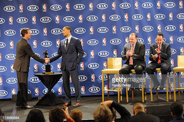 Derrick Rose of the Chicago Bulls is congratulated by Tim Chaney of Kia Motors as Bulls Head Coach Tom Thibodeau and General Manager Gar Forman look...