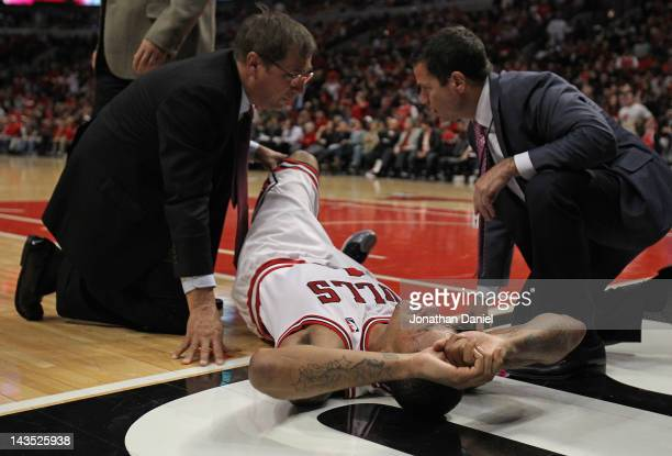 Derrick Rose of the Chicago Bulls is examined after suffering an injury against the Philadelphia 76ers in Game One of the Eastern Conference...