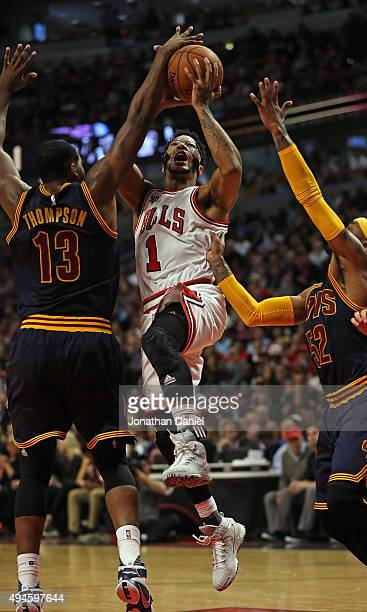 Derrick Rose of the Chicago Bulls is fouled as he tries to drive between Tristan Thompson and Mo Williams of the Cleveland Cavaliers during the...