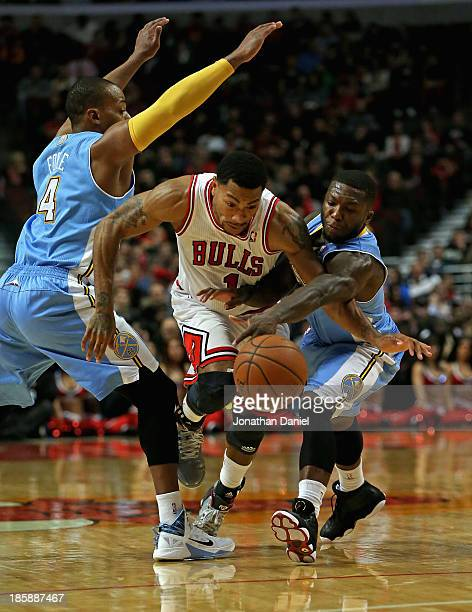Derrick Rose of the Chicago Bulls is fouled by Nate Robinson of the Denver Nuggets as he drives between Robinson and Randy Foye during a preseason...