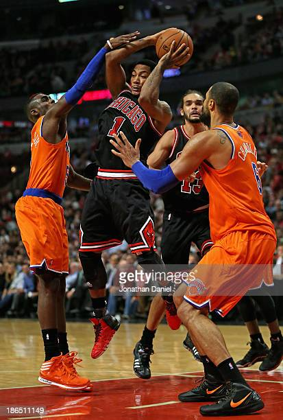 Derrick Rose of the Chicago Bulls leaps to pass between Tim Hardaway Jr #5 and Tyson Chandler of the New York Knicks at the United Center on October...