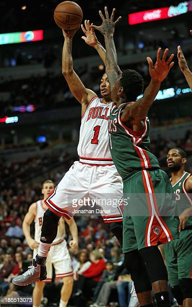 Derrick Rose of the Chicago Bulls leaps to pass over Larry Sanders of the Milwuakee Bucks during a preseason game at the United Center on October 21...