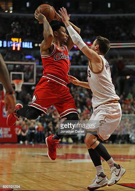 Derrick Rose of the Chicago Bulls leaps to pass over Matthew Dellavedova of the Cleveland Cavaliers at the United Center on April 9 2016 in Chicago...