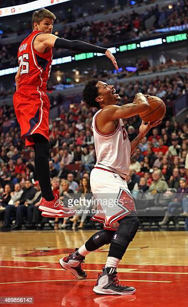 Derrick Rose of the Chicago Bulls looses the ball after being hit by Kyle Korver of the Atlanta Hawks at the United Center on April 15 2015 in...