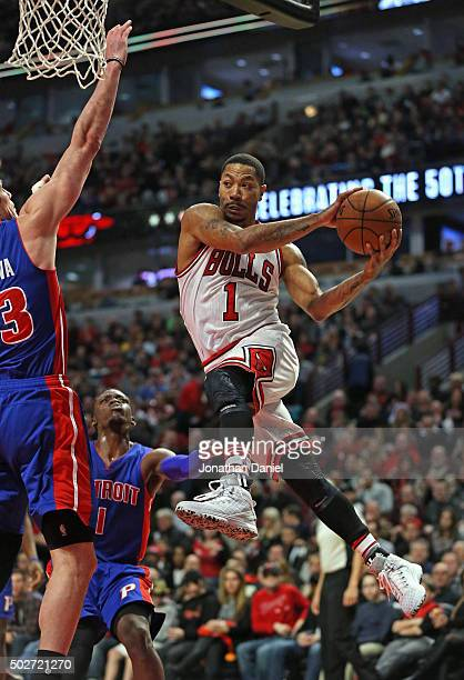 Derrick Rose of the Chicago Bulls passes around Ersan Ilyasova of the Detroit Pistons at the United Center on December 18 2015 in Chicago Illinois...