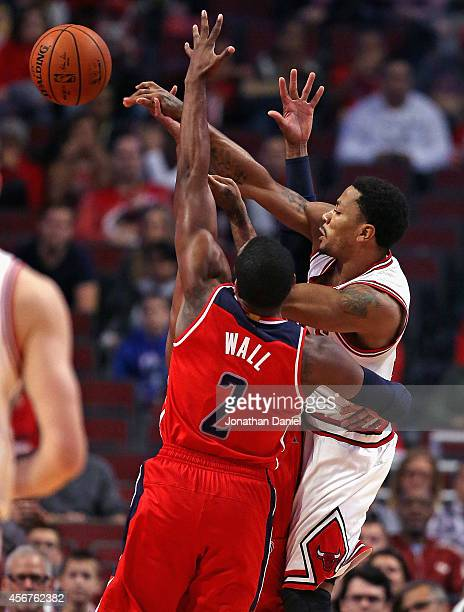 Derrick Rose of the Chicago Bulls passes between John Wall and Paul Pierce of the Washington Wizards during a preseason game at the United Center on...