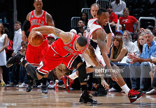 Derrick Rose of the Chicago Bulls protecs the ball from Jeff Teague of the Atlanta Hawks in Game Three of the Eastern Conference Semifinals in the...