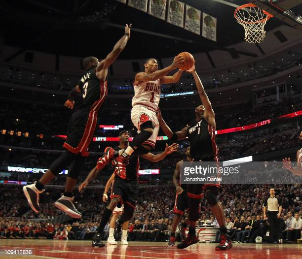 Derrick Rose of the Chicago Bulls puts up a shot between Dwyane Wade and Chris Bosh of the Miami Heat at the United Center on February 24 2011 in...