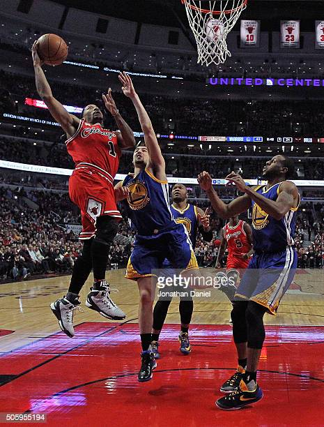 Derrick Rose of the Chicago Bulls puts up a shot over Klay Thompson and Draymond Green of the Golden State Warriors on his way to a gamehigh 29...