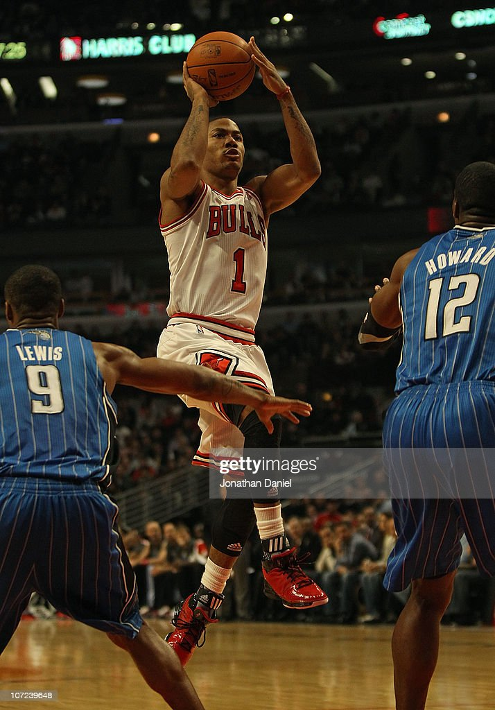 Derrick Rose #1 of the Chicago Bulls shoots against Rashard Lewis #9 and Dwight Howard #12 of the Orlando Magic at the United Center on December 1, 2010 in Chicago, Illinois. The Magic defeated the Bulls 107-78.