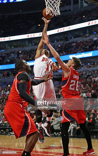 Derrick Rose of the Chicago Bulls shoots over Paul Millsap and Kyle Korver of the Atlanta Hawks at the United Center on April 15 2015 in Chicago...