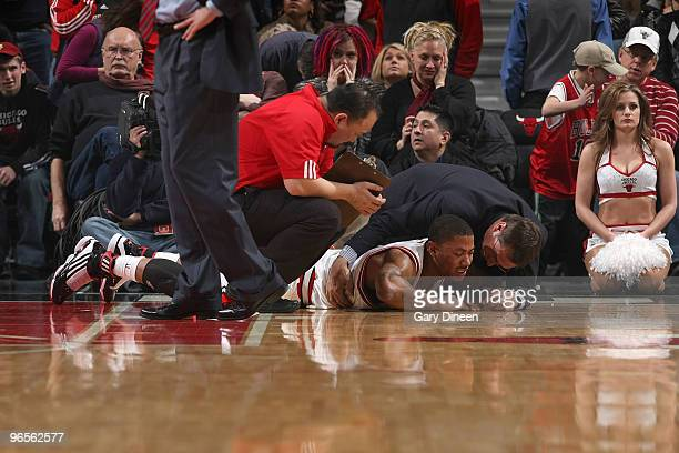 Derrick Rose of the Chicago Bulls talks to team staff after bruising his right hip in a collision with Dwight Howard of the Orlando Magic on February...