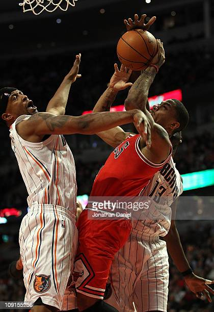 Derrick Rose of the Chicago Bulls tries to shoot under pressure from Dominic McGuire and Nazr Mohammed of the Charlotte Bobcats at the United Center...