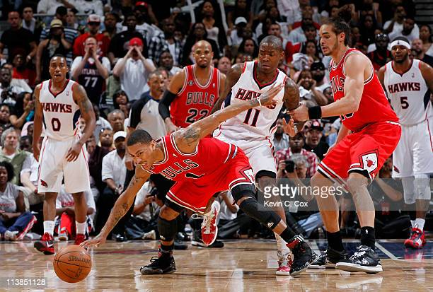 Derrick Rose of the Chicago Bulls turns over the ball as he loses it against Jamal Crawford of the Atlanta Hawks in Game Four of the Eastern...