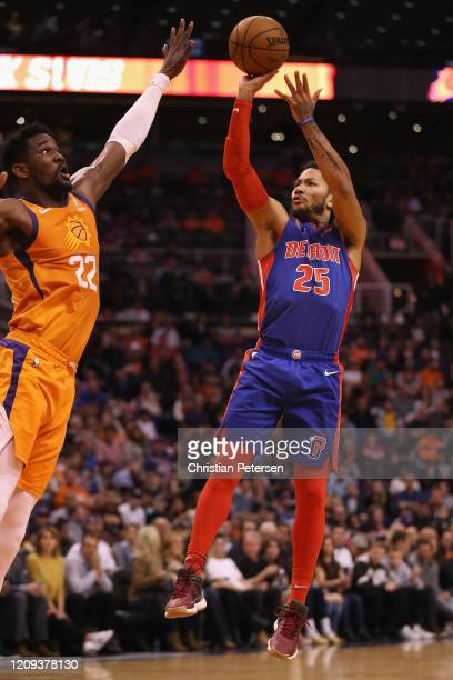Derrick Rose of the Detroit Pistons attempts a shot over Deandre Ayton of the Phoenix Suns during the first half of the NBA game at Talking Stick...
