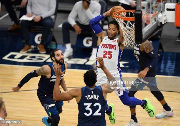 Derrick Rose of the Detroit Pistons passes the ball against Ricky Rubio and Karl-Anthony Towns of the Minnesota Timberwolves during the fourth...