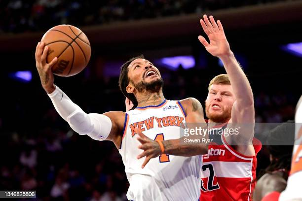 Derrick Rose of the New York Knicks attempts a shot against Davis Bertans of the Washington Wizards during a preseason game at Madison Square Garden...