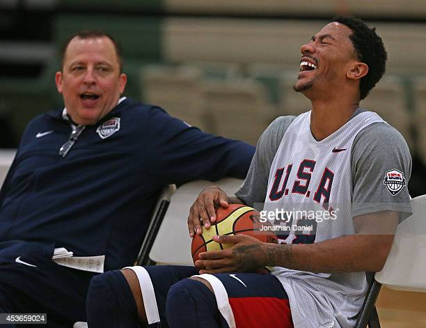 Derrick Rose, wearing, laughs at a story told by assistant USA coach and his head coach of the Chicago Bulls, Tom Thibodeau, during a USA basketball...