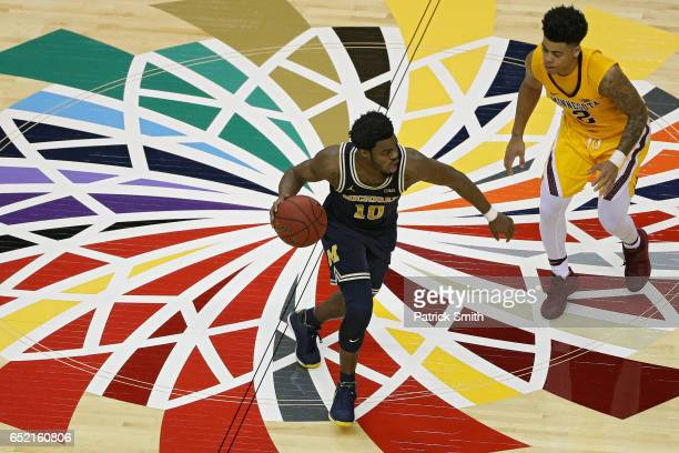 Derrick Walton Jr #10 of the Michigan Wolverines dribbles in front of Nate Mason of the Minnesota Golden Gophers during the second half in the...