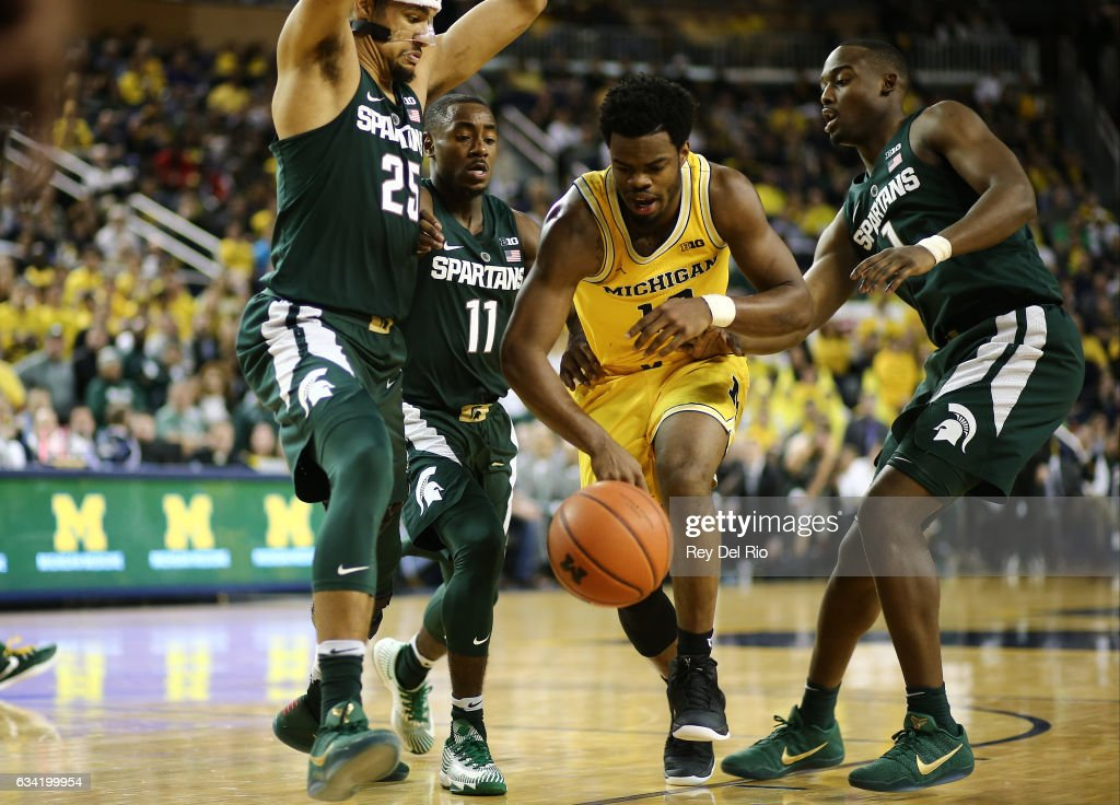 Derrick Walton Jr. #10 of the Michigan Wolverines splits the Michigan State Spartans defense at Crisler Arena on February 7, 2017 in Ann Arbor, Michigan.