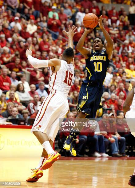 Derrick Walton Jr #10 of the Michigan Wolverines takes a three point shot as Naz Long of the Iowa State Cyclones defends in the first half of play at...