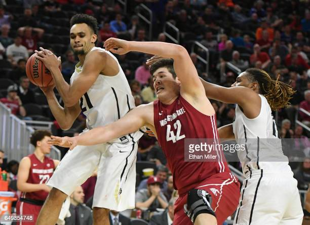 Derrick White of the Colorado Buffaloes grabs a rebound against Conor Clifford of the Washington State Cougars as Xavier Johnson of the Cougars...