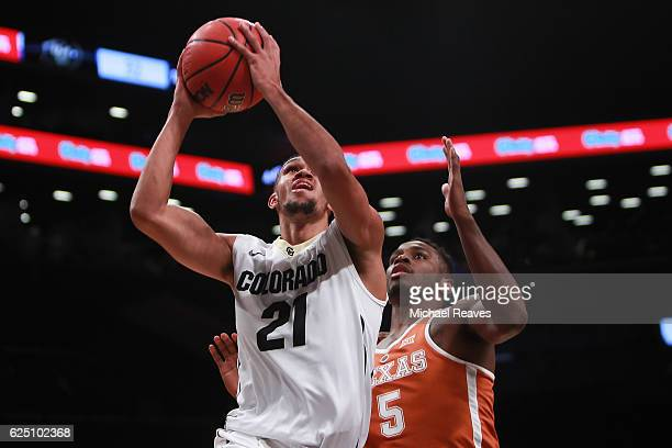 Derrick White of the Colorado Buffaloes puts up a layup over Kendal Yancy of the Texas Longhorns in the second half during the consolation game of...