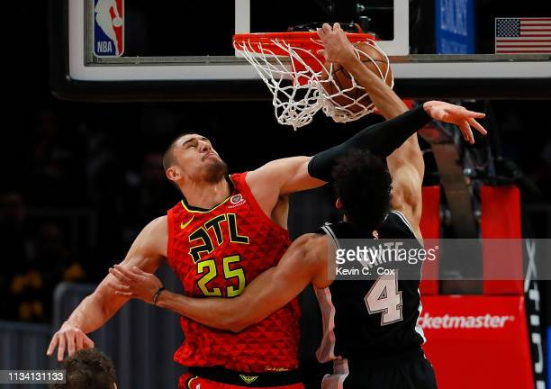 Derrick White of the San Antonio Spurs dunks against Alex Len of the Atlanta Hawks in the first half at State Farm Arena on March 06 2019 in Atlanta...