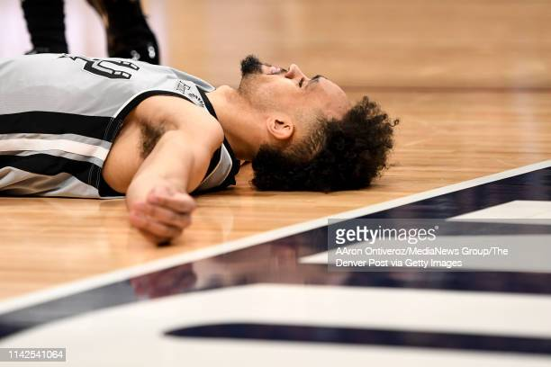 Derrick White of the San Antonio Spurs lies on the ground after committing a foul on Torrey Craig of the Denver Nuggets during the fourth quarter of...