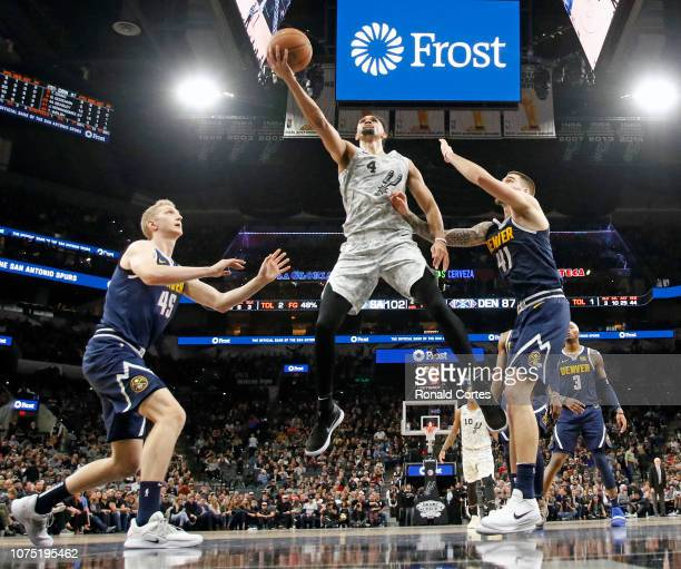 Derrick White of the San Antonio Spurs scores between Juan Hernangomez of the Denver Nuggets and Thomas Welsh at ATT Center on December 26 2018 in...