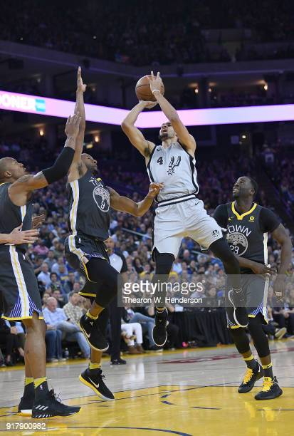 Derrick White of the San Antonio Spurs shoots over Andre Iguodala of the Golden State Warriors during an NBA basketball game at ORACLE Arena on...
