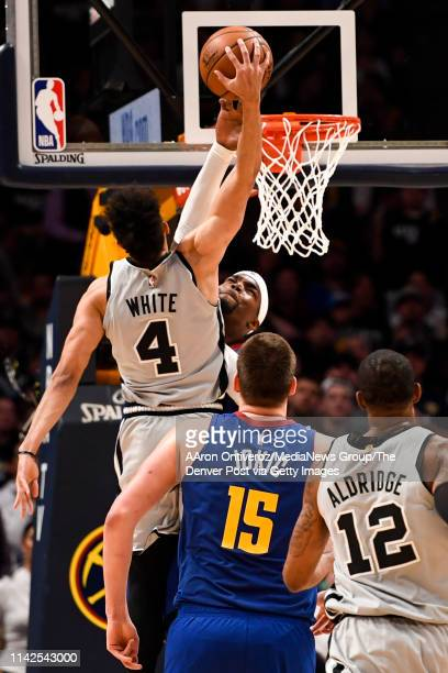 Derrick White of the San Antonio Spurs throws down on Paul Millsap of the Denver Nuggets during the third quarter of the Spurs' 10196 win on Saturday...