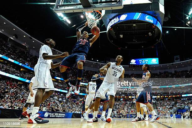 Derrick Williams of the Arizona Wildcats dunks the ball against Roscoe Smith and Charles Okwandu of the Connecticut Huskies during the west regional...