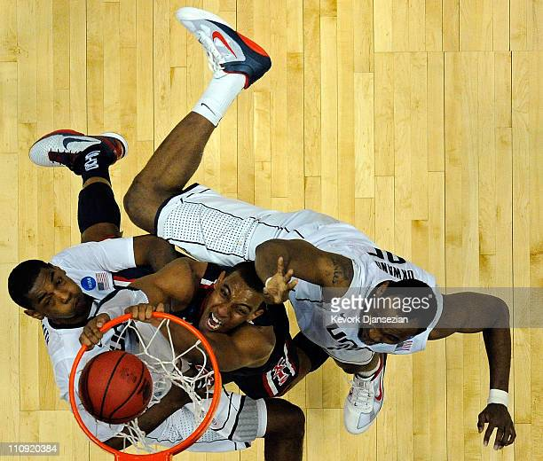 Derrick Williams of the Arizona Wildcats dunks the ball against Charles Okwandu and Roscoe Smith of the Connecticut Huskies during the west regional...