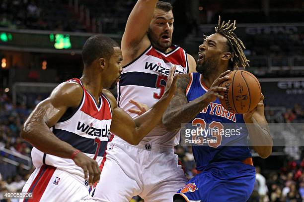 Derrick Williams of the New York Knicks is defended by Josh Harrellson and Ramon Sessions of the Washington Wizards during the first half at Verizon...