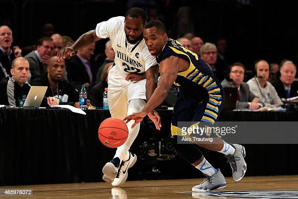Derrick Wilson of the Marquette Golden Eagles and JayVaughn Pinkston of the Villanova Wildcats battle for a loose ball in the first half during a...