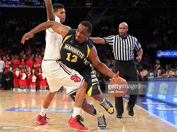 Derrick Wilson of the Marquette Golden Eagles drives to the basket against Jamal Branch of the St John's Red Storm during the game at Madison Square...