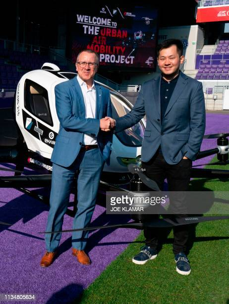Derrick Xiong cofounder CMO of EHang and Robert Machtlinger CEO of FACC shake hands as they pose with an Air Taxi EHANG 216 during a press preview of...