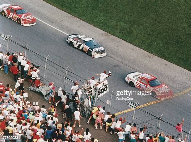 Derrike Cope driver of the Chevrolet Lumina crosses the finish line first as Terry Labonte driver of the Skoal Classic Oldsmobile and Bill Elliott...