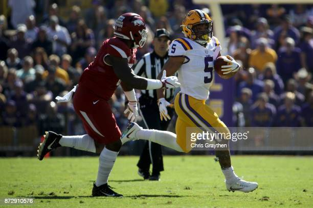 Derrius Guice of the LSU Tigers avoids a tackle by De'Jon Harris of the Arkansas Razorbacks at Tiger Stadium on November 11 2017 in Baton Rouge...