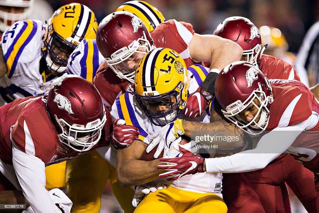 Derrius Guice #5 of the LSU Tigers is tackled by a group of defensive players of the Arkansas Razorbacks at Razorback Stadium on November 12, 2016 in Fayetteville, Arkansas. The Tigers defeated the Razorbacks 38-10.