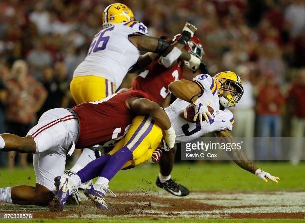 Derrius Guice of the LSU Tigers is tackled by Raekwon Davis of the Alabama Crimson Tide at BryantDenny Stadium on November 4 2017 in Tuscaloosa...