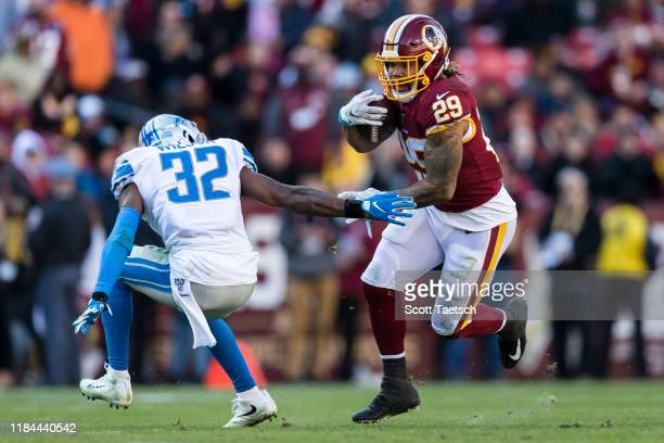 Derrius Guice of the Washington Redskins carries the ball as Tavon Wilson of the Detroit Lions defends during the first half at FedExField on...