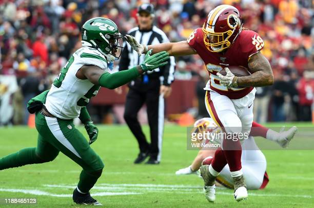 Derrius Guice of the Washington Redskins runs in front of James Burgess of the New York Jets during the first half at FedExField on November 17, 2019...